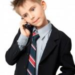 Dreng i jakkesæt med slips taler i mobiltelefon