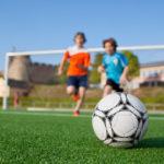 2-drenge-traener-fodbold-foran-fodboldmaal